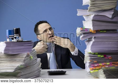 Exhausted Office Worker Yawns Tired Of Looking At Huge Stack Of Documents. Fatigue And Overload Conc