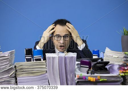 Busy Overworked Business Man Employee Sitting At Table With Piles Of Papers In Office. Fatigue And O