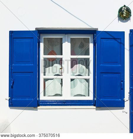 Window of a greek whitewashed house with trditional blue shutters in Mykonos island, Greece