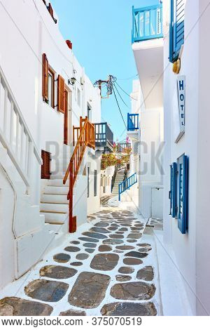 Perspective of old street with whitewashed houses in Mykonos, Greece - Greek cityscape