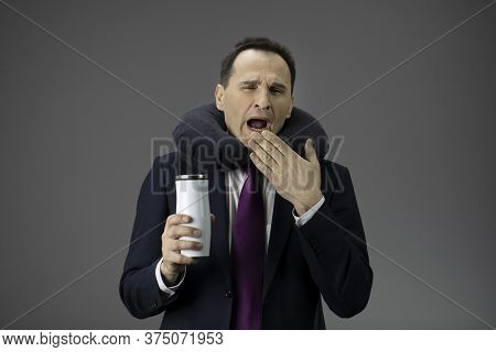 Handsome Middle-aged Businessman In Suit Yawns With Mug Of Coffee In His Hand And Inflatable Pillow