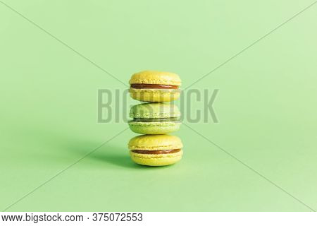 Tasty French Macaroons On A Light Green Pastel Background.  Pistachio And Caramel Macaroons. Place F