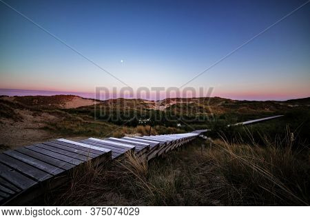 Steps On Coastal Wooden Boardwalk After Sunset With Colorful Purple Sky Over Rolling Sand Dunes And