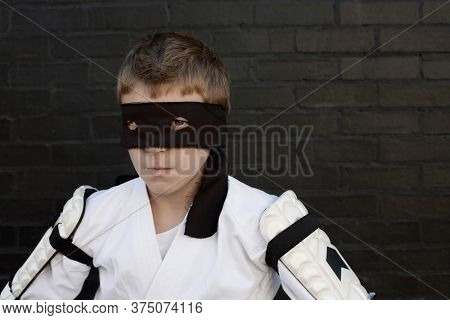 Boy wearing Zorro blindfold and fencing costume