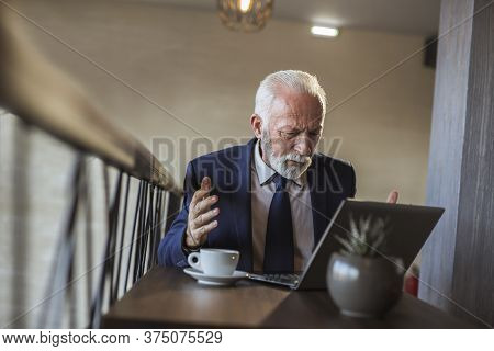 Senior Businessman In A Restaurant, Analysing Financial Data And Reports Using Laptop Computer, Disp