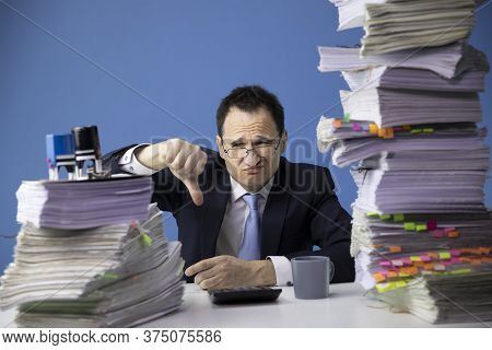 Businessman In Glass And Tie Shows Finger Down Sitting At Office Desk With Huge Stack Of Documents L