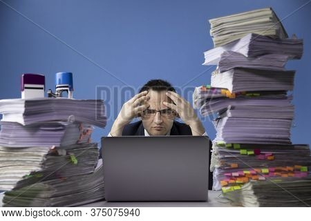 Tired Concerned Businessman In Glass And Tie Sitting At Office Desk With Huge Pile Of Documents Work