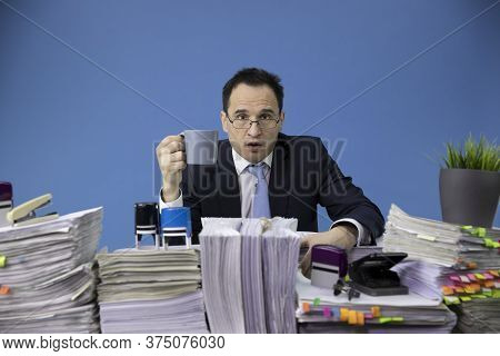 Businessman Angrily Looking At Camera With Cup Of Coffee In His Hand At Desk Full Of Paperwork, Invo