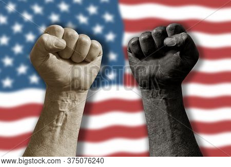 Raised Black And White Clenched Fist In Front Of Blurred Waving American Flag. Diversity Segregation