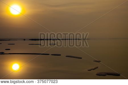 The foggy sun is reflected in the surface of the water. Dead Sea. Evaporated salt protrudes above water. The concept of active, environmental and photo tourism