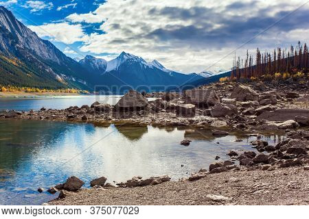 Canada, Alberta, Jasper. Great autumn day. The magical beauty of a mountain lake. The sun illuminates the snow-capped mountains. The rocky shore of the mountain lake of Medicine