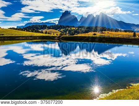 Beautiful sunny summer day in hilly valley Alpe di Siusi. Italy. In the water of a small pond, the sky and sun are reflected. The concept of walking, ecological and photo tourism