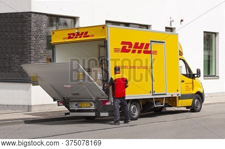 Delivery Man In Uniform Opening Tailgate Loader On A Dhl Lorry. Courier, Parcel, And Express Mail Se