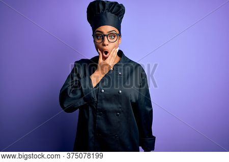 Young african american chef girl wearing cooker uniform and hat over purple background Looking fascinated with disbelief, surprise and amazed expression with hands on chin