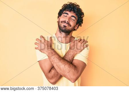 Handsome young man with curly hair and bear wearing casual tshirt over yellow background hugging oneself happy and positive, smiling confident. self love and self care