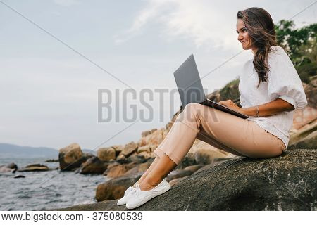 Young, Smiling Girl Working Using A Laptop, Sitting On A Rocky Seashore. Business Woman Working On R