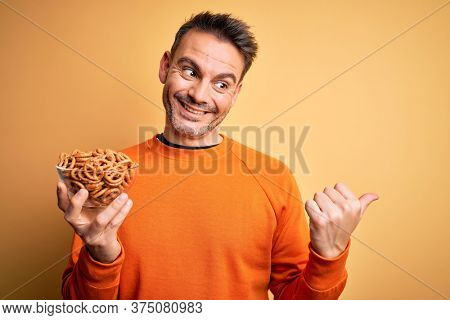 Young handsome man holding bowl with german baked pretzels over yellow background pointing and showing with thumb up to the side with happy face smiling