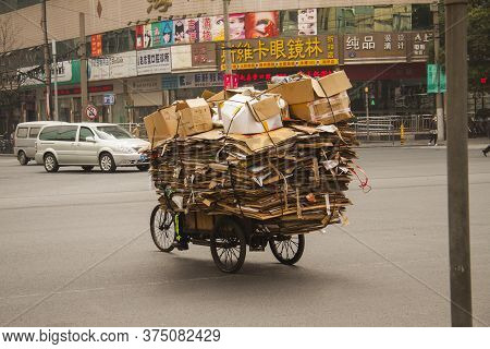 Chinese Man Riding A Cargo Tricycle Loaded With Cardboard Waste On A Road In China. Cargo Bikes Or F