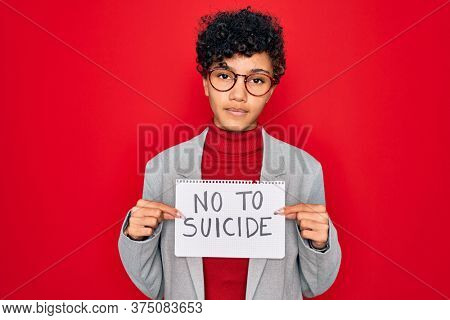 Beautiful african american afro businesswoman holding banner with no to suicide message with a confident expression on smart face thinking serious