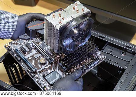 Assembling Desktop Computer. Serviceman Installs Motherboard In Computer Case. Personal Computer