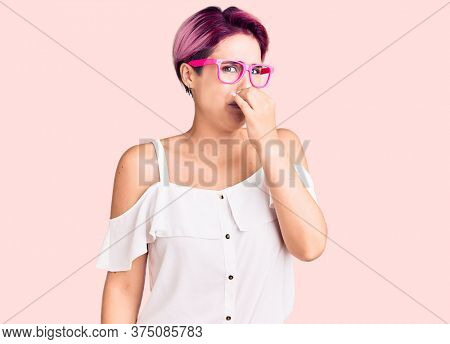 Young beautiful woman with pink hair wearing casual clothes and glasses smelling something stinky and disgusting, intolerable smell, holding breath with fingers on nose. bad smell