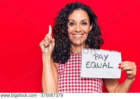 Middle age beautiful woman holding pay equal paper smiling with an idea or question pointing finger with happy face, number one