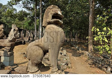 Ancient Stone Sculpture Of A Mythological Lion In The Temple Of Angkor. A Lion Sits On Stones Among