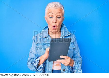 Senior beautiful woman with blue eyes and grey hair using touchpad device scared and amazed with open mouth for surprise, disbelief face