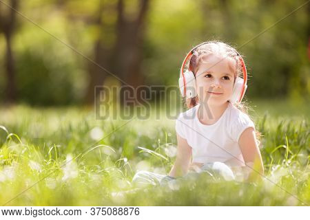 Cute little girl is listening to music in the park. Family outdoor lifestyle. Happy small kid in headphones sitting on green grass. Beauty nature at summer. Childhood happiness.  Children day.