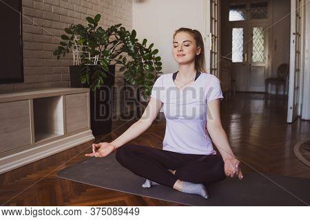 Young Woman Practicing Yoga Exercises At Home. Padmasana / Lotus Position