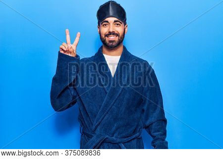 Young hispanic man wearing sleep mask and robe smiling with happy face winking at the camera doing victory sign. number two.