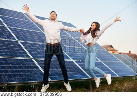 Young Cheerful Man And Woman Jumping Holding Hands By A Solar Panel, Wearing Similar Clothes, Concep