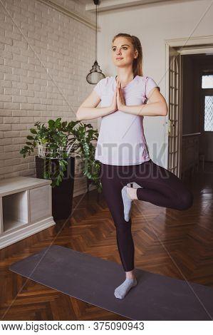 Young Woman Practicing Yoga Exercises At Home. Vrikshasana / Tree Pose