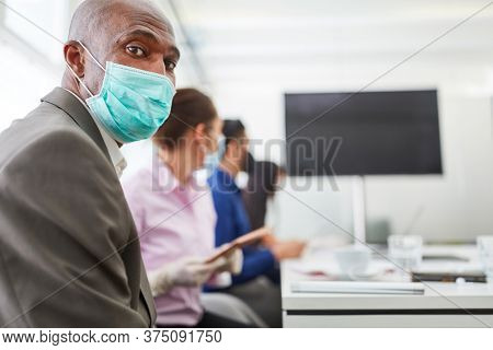 African business man with face mask because of Covid-19 in a videoconference meeting