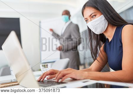 Businesswoman with face mask because of Covid-19 and corona virus works on laptop computer in the office