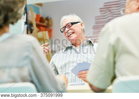 Vital senior plays cards with other seniors in retirement home or at home