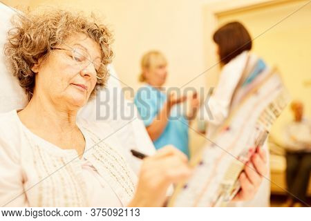 Senior woman as a patient solves puzzles in bed in the hospital or nursing home