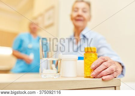 Nursing assistance and senior woman with various medications in assisted living