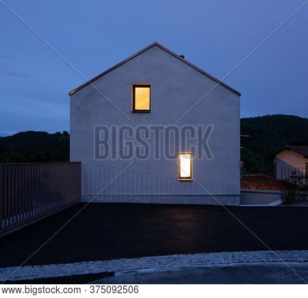 Single-family house facade in Switzerland, evening and almost night situation with two yellow illuminated windows. Romantic and silent photo. A fairy tale
