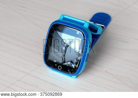 Multicolored Kids Smart Watch Phone With Broken Screen On A Light Wooden Table. Technology For Child