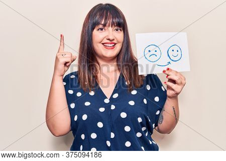 Young plus size woman holding sad to happy emotion paper smiling with an idea or question pointing finger with happy face, number one