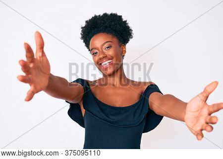 Young african american woman wearing casual clothes looking at the camera smiling with open arms for hug. cheerful expression embracing happiness.