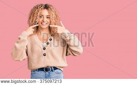 Young blonde woman with curly hair wearing casual winter jumper smiling cheerful showing and pointing with fingers teeth and mouth. dental health concept.
