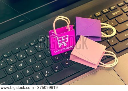 Online Shopping Concept, Three Colorful Paper Shopping Bags On Notebook Keyboard. E-commerce Is The