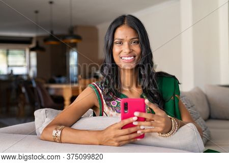 Portrait of smiling indian woman in traditional sari using smart phone. Indian woman sitting on couch while holding cellphone and looking at camera. Beautiful hindu wife with bindi surfing the net.