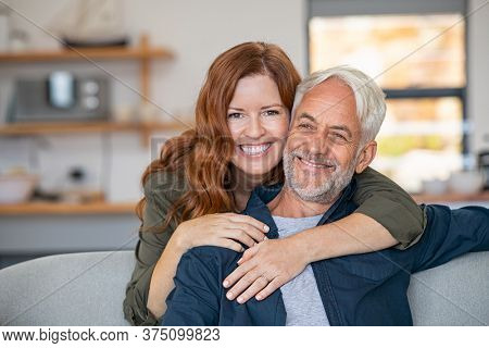 Smiling woman hugging her senior husband on couch from behind in the living room. Loving retired couple looking at camera and smiling at home. Portrait of smiling woman embracing mature man on sofa.