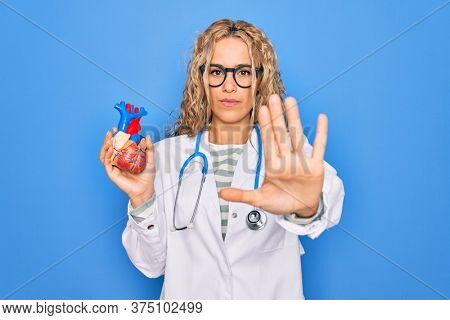 Young beautiful blonde cardiologist woman wearing stethoscope holding plastic heart with open hand doing stop sign with serious and confident expression, defense gesture
