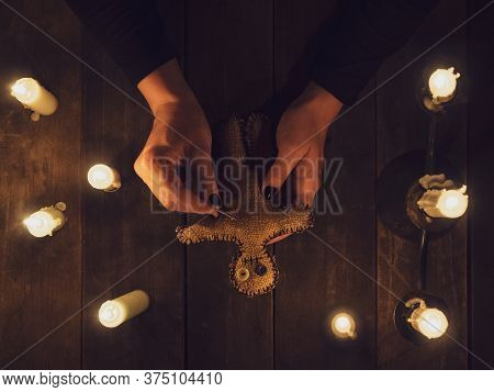 A Witch In The Dark Holds A Voodoo Rag Doll Surrounded By Candles, Flat Lay. The Concept Of Black Ma
