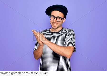 Handsome man with blue eyes wearing striped t-shirt and french beret over purple background clapping and applauding happy and joyful, smiling proud hands together