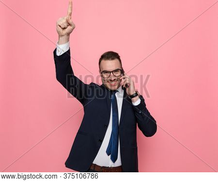 enthusiastic young guy in suit talking on the phone and pointing finger in the air, smiling and standing on pink background